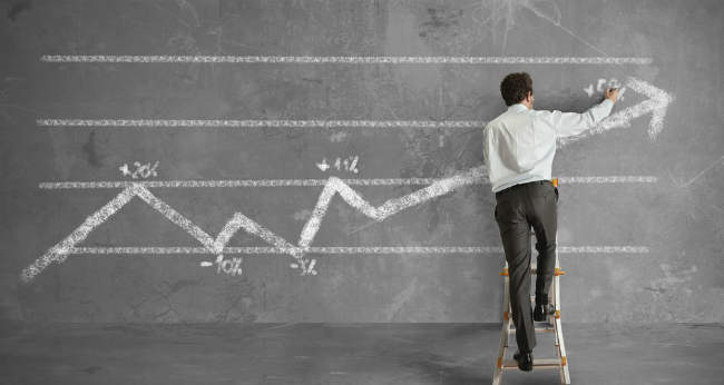 データを黒板に書き込むビジネスマン