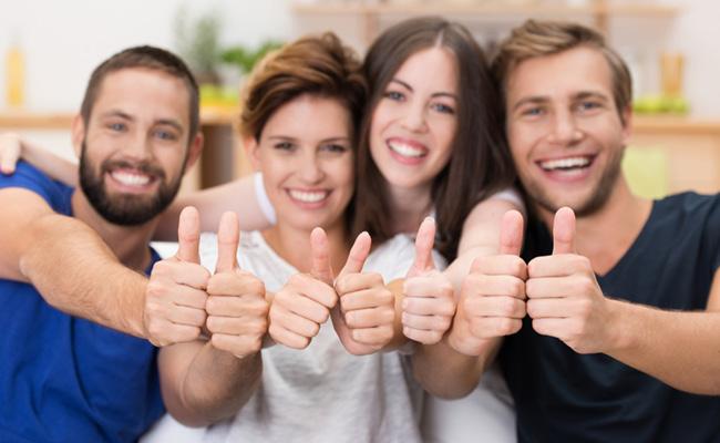 男女4人が笑顔で親指を立てている写真