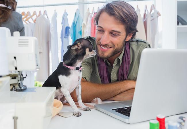 ノートパソコンで仕事する男性とその飼い犬