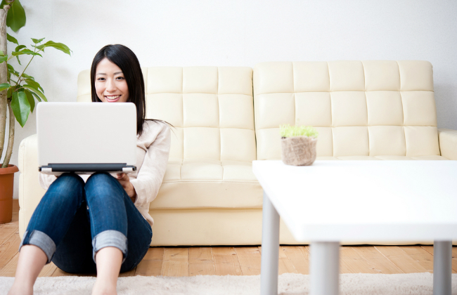 ノートパソコンを持って笑顔で作業する女性