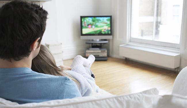 テレビを見ながらリラックスする男性