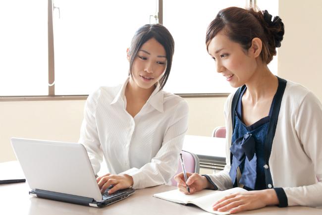 ノートパソコンでドメイン名を話し合う女性二人
